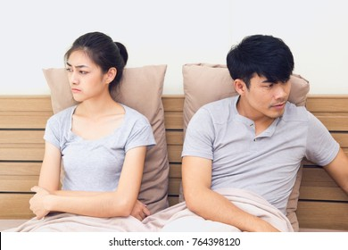 Couple relationship concepts. Young asian man trying to reconcile with his girlfriend after have an argument on bed. woman heartbroken with his bad word.
