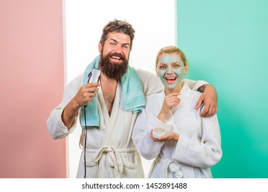 Couple. Relationship. Family life. Husband and wife. Happy woman with cosmetic facial mask. Bearded man with electric shaver trimming beard. Morning treatments. Morning routine. Morning procedures.