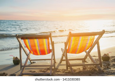 Couple relax chair on sand beach with warm sunset - vacation in beautiful sea nature concept