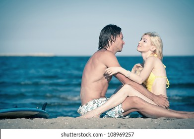 Couple relaxing at the beach with surfboard.