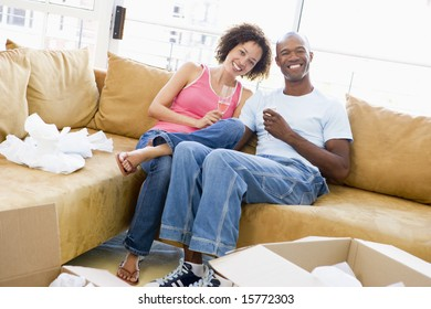 Couple relaxing with champagne by boxes in new home smiling