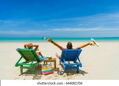 Couple Relaxing in Deck Chairs on the Tropical Beach