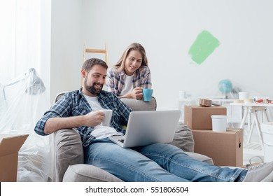 Couple relaxing during home renovation, they are connecting with a laptop and having a coffee break