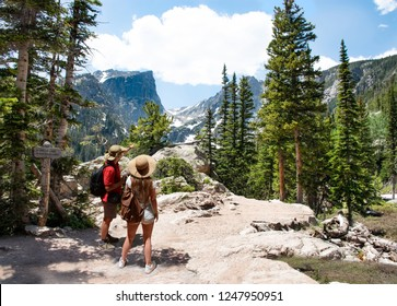 Couple relaxing and enjoying beautiful mountain view. Man and woman with backpacks hiking on Emerald Lake trail.Early summer landscape with snow covered mountains.Rocky Mountains National Park, USA