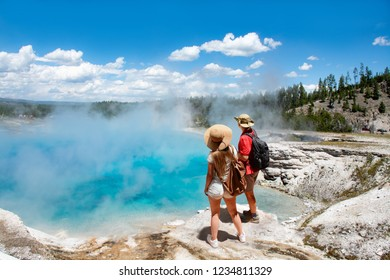 Couple relaxing and enjoying beautiful view of gazer on vacation hiking trip. Man and woman with backpacks looking at Excelsior Geyser from the Midway Basin in Yellowstone National Park. Wyoming, USA