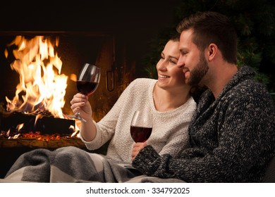 Couple relaxing with glasses of red wine at romantic fireplace on winter evening