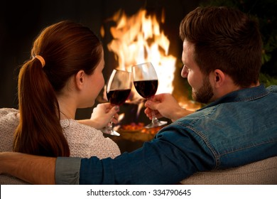 Couple relaxing with glasses of wine at romantic fireplace on winter evening