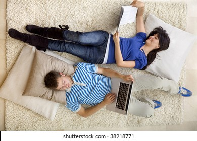 Couple relaxing at home with a laptop and reading