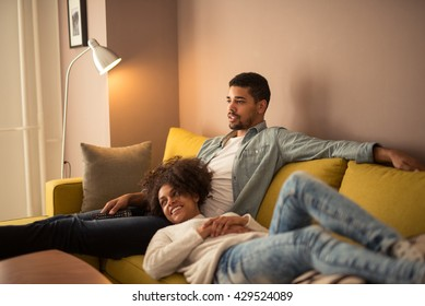 Couple relaxing at home and watching tv together.