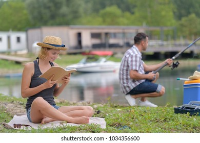 couple relaxing in nature fishing and reading