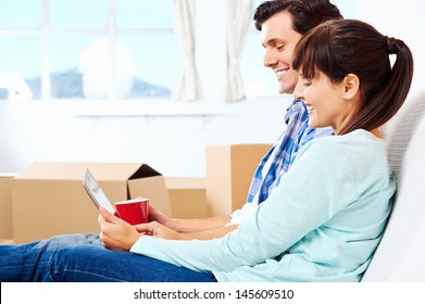 couple relaxing in new home with tablet computer on sofa couch