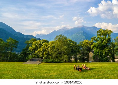 A couple relaxing on the grass during a pleasant afternoon in Bellinzona, Ticino, Switzerland.