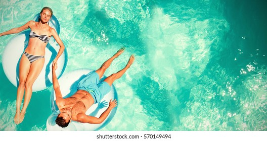 Couple relaxing on lilos in swimming pool