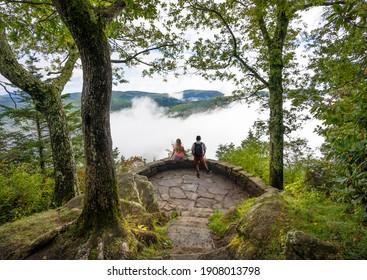 Couple relaxing on top of the mountain on summer hiking trip. Friends enjoying beautiful view. Near  Asheville, Blue Ridge Parkway, North Carolina, USA.