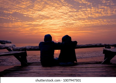 Couple relaxing on wooden terrace and looking to Sunrise on the beach.