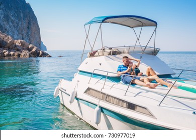Couple relaxing on a yacht at sea on the background of a beautiful mountain landscape. Happy wealthy man and a woman by private boat have sea trip.