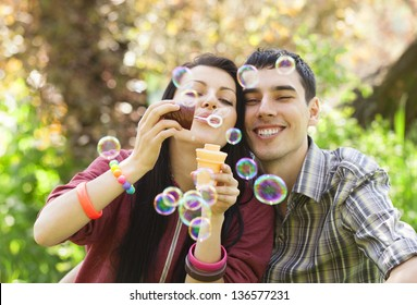 Couple Relaxing in the Park with bubble blower. Spring time