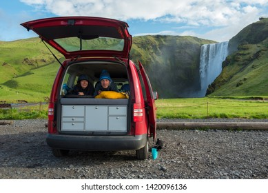 Couple relaxing in a red minivan in sleeping bags with opened back door. Skogafoss waterfall in the background, Iceland