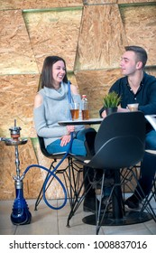 couple relaxing and smoking hookah at caffe bar. social concept