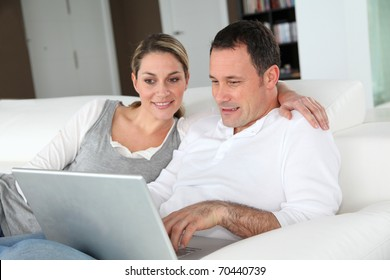 Couple relaxing in sofa with laptop computer