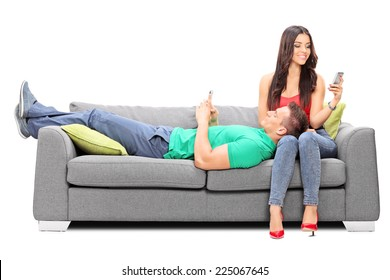 Couple relaxing with their cell phones on a sofa isolated on white background