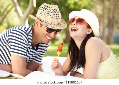 Couple Relaxing Together In Garden Eating Ice Lolly