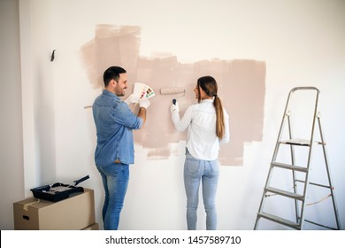 Couple renovating their apartment while man holding color palette and woman painting walls with roller.