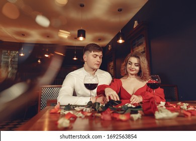 Couple in a restaurant. Lady in a red dress. Pair drinking a vine. Valentine's day.