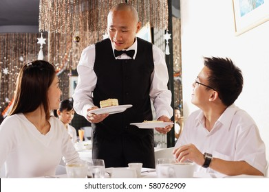 Couple in restaurant, waiter standing, holding plates of dessert