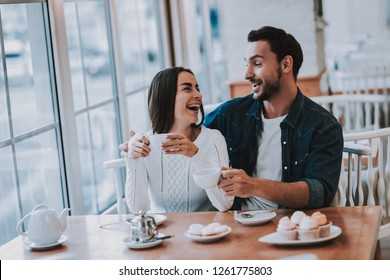 Couple Resting in Cafe. Couple is Beautiful Young Man and Woman. Couple is Drinking Tea. People is Looking on Each Other. Persons is Sitting at Table. People is Happy and Smiling. Daytime.
