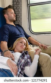 Couple resting with eyes closed in train sleeping woman man