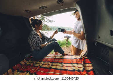 couple resting outside. car travel concept. sitting in trunk