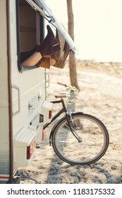 couple resting in trailer with feet outside, bicycle near campervan