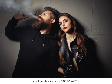 Couple resting in vape shop, to let smoke out of mouth. Bearded man and young woman smoking e-cigarettes with lowe angle view off the middle-aged man exhaling smoke from his nostrils in the foreground