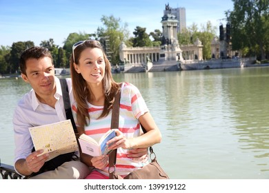 Couple in Retiro Park of Madrid looking at map
