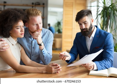 Couple reviews financial documents with advisor.