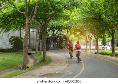 couple ride bicycles in the morning at public park.