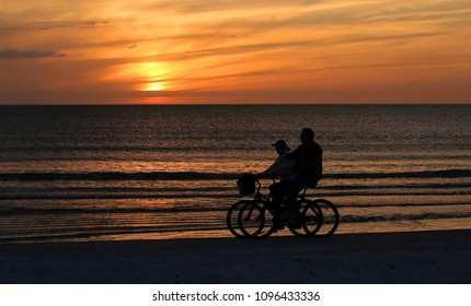 Couple ride side by side enjoying the sunset and getting their exercise on beautiful Fort Myers Beach, Florida, USA.