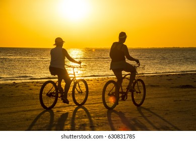 Couple rides bicycles in sunset rays on Sanibel Island.