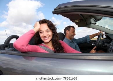 Couple riding convertible car