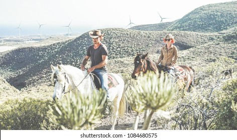 Couple riding horses in countryside nature tour - Happy people having fun on summer day - Vacation, excursion, healthy lifestyle, sport, love between people and animals concept - Main focus on girl