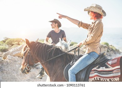 Couple riding horses in countryside on excursion nature tour - Happy people having fun on summer day - Vacation, excursion, healthy lifestyle, sport concept - Focus on woman head