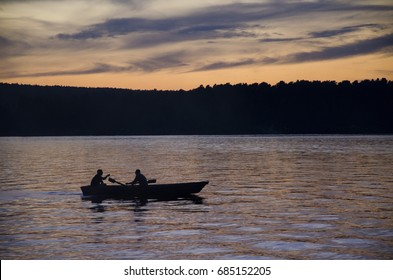 The couple is riding on the row boat at the sunset sky and tranquil lake for pleasure and fishing