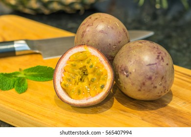 A couple of ripe passion fruit with a cut half in front