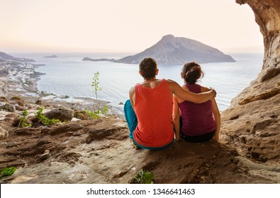 Couple of rock climbers having rest while sitting at bottom of cliff and enjoying picturesque view of Telendos Island in front. Kalymnos Island, Greece.