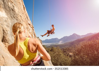 Couple of rock climbers - woman holding man with belay rope against the blue sky and mountains. Stock photo.