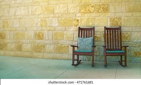 A couple of rocking chairs by yellow stone wall