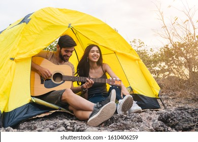 Couple romantic camping on mountain sitting in tent with guitar evening time, camping travel concept.