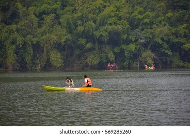 Couple are Rowing, kayaking and canoeing with fog over the lake and mountain in  the morning, Khoa Wong reservoir,Suphanburi  , Central of Thailand