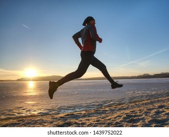 Couple runners running in winter nature. Frozen river beach run. Copy space.